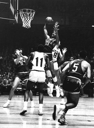 Wilt Chamberlain - Chamberlain grabs a rebound during a game against the New York Knickerbockers.