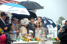 Happy group of people standing under umbrellas looking at silver trophies