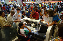 Busy interior of an airport terminal, with people crowding around a ticket counter, where a woman ticket agent is seated, listening patiently to an animated customer waving her hand.