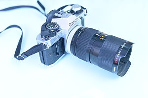 Zoom lens - Canon AE-1, a 35mm camera with a zoom lens. The advantage of a zoom lens is the flexibility, but the disadvantage is the optical quality. Prime lens have a greater image quality in comparison.