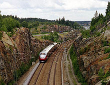 A four-car multiple unit running along a double-track line between two cliffs; in the background is a motorway.
