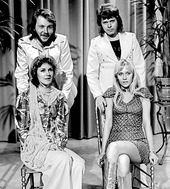 Black-and-white image of ABBA, with the male members standing while the female members sitting in front.