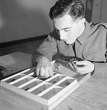 A man sorts small objects into a wooden tray
