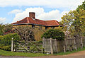 A house with fence and flowering tree at Matching Tye, Essex, England.jpg