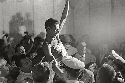Bikila lifted above a crowd in celebration