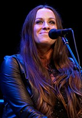 An image of a woman with long brown hair and a leather jacket. She is looking toward the camera while performing on stage.