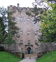 A tall stone building from the 15th century with trees bordering to the sides
