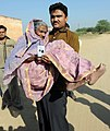 An elderly woman being carried to cast her vote at the polling booth of Palri Meena, Bagru, in Jaipur, during the Rajasthan Assembly Election, on December 01, 2013.jpg