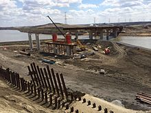 Berms were used for construction of two steel bridges carrying Anthony Henday Drive over the North Saskatchewan River in northeast Edmonton, first on the river's south bank, then the north bank seen here in 2014. The bridges carry three lanes northbound and four lanes southbound.