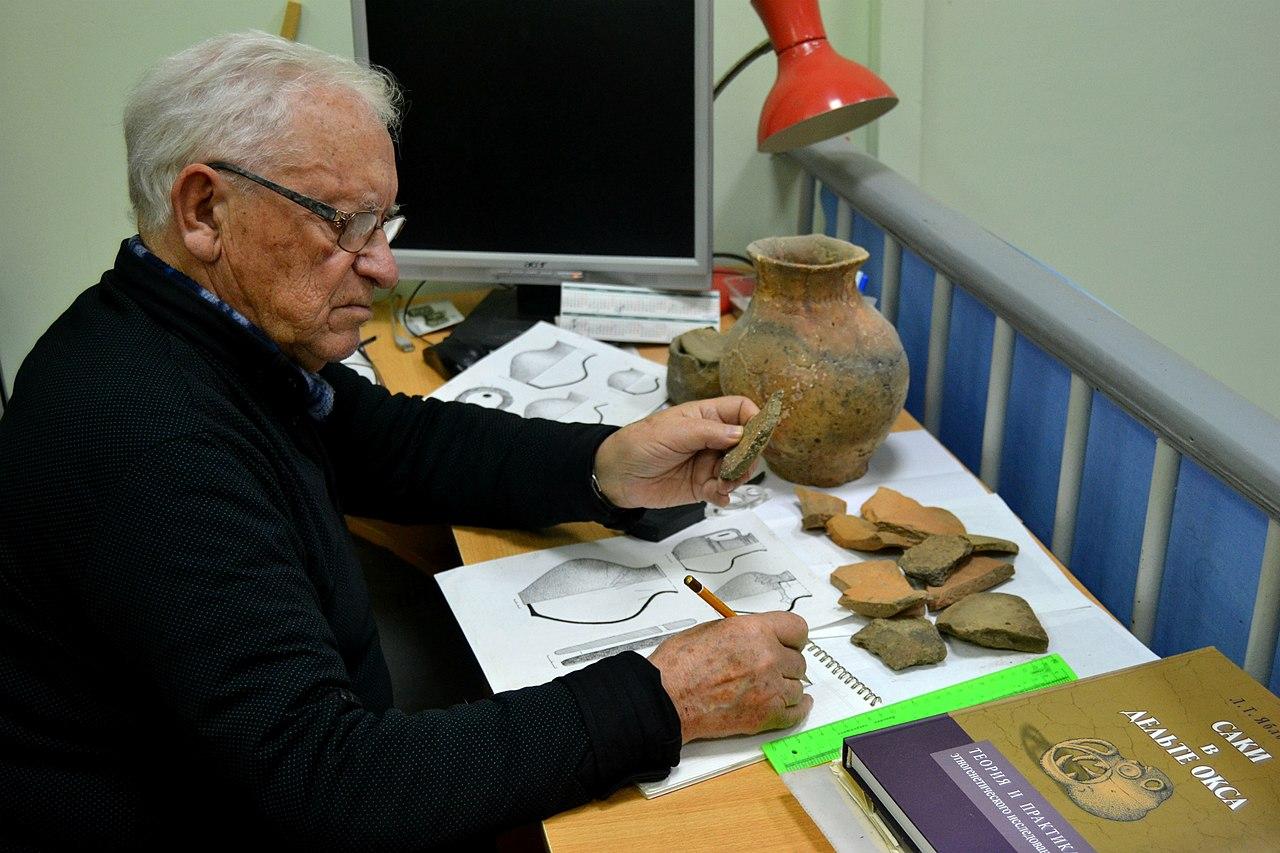 L'archéologue russe Vladislav Ivanovich Mamontov en train d'identifier des céramiques à partir de catalogues de comparaison