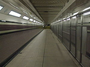 Arsenal tube station - Passageway linking the tunnels to the ticket office, looking towards the latter. Note tidal flow segregation, in operation on football match days (fans using the wider section).