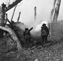 Black and white photo of two WWI soldiers running towards enemy lines