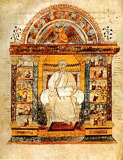 Manuscript illustration of a bearded, white-haired man in white toga, holding a book open, with his other hand at his chin. The man is sitting in a chair in a golden niche, surmounted by a portrait of a winged bull under an arch; at either side of the niche are twelve small group scenes from the Life of Christ (see article on the manuscript for a detailed description).
