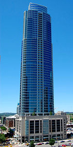 Slightly elevated view of a 60-story skyscraper with a glass facade set atop a rectangular pedestal; the building has balconies on every floor and has two small setbacks near the roofline.