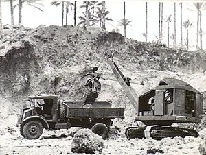 Landing at Jacquinot Bay - A power shovel operated by the 2/3rd Railway Construction Company unloading gravel to be used for road building in the Jacquinot Bay area into a truck