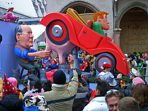 "German humour - A carnival float during the Rosenmontagzug in Cologne (Cologne Carnival) in 2006: a driver gets ""milked"" (i.e., fleeced) by the former finance minister Peer Steinbrück."