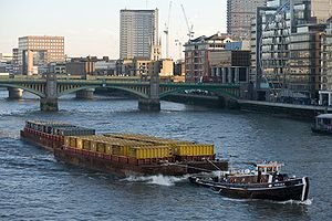 Barge - Barges towed by a tugboat on the River Thames in London, England, UK