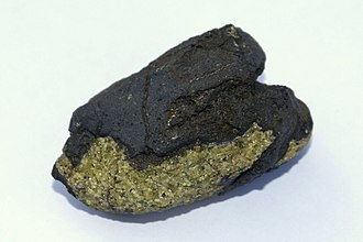 Basanite - Volcanic bomb of black basanite enclosing a xenolith of green dunite from Réunion