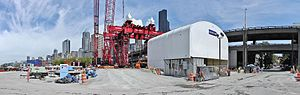 Bertha (tunnel boring machine) - View of retrieval site for repairs of Bertha's cutter head. The red gantry crane, center, was used to lift the cutter head from a shaft dug in front of the stuck boring machine. The white shed, right, was built to house the head during repairs and upgrades, and then the head was lowered back down the shaft and reinstalled.