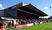 One of the stands of the Bootham Crescent association football ground, with supporters sitting down and a grass field below