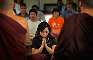 Asian person holding hands in prayer, facing two monks in brown robes.