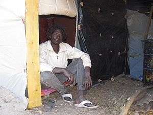 Migrants around Calais - A Sudanese migrant sits in his self-constructed cottage in the New Jungle, June 2015