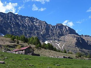 "Alps - An ""Alp"" refers to a high mountain pasture, often with a structure, such as this one on the south side of the Alps, where cows are taken for grazing."