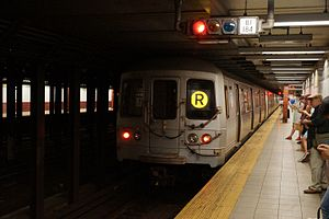 R (New York City Subway service) - A train made of R46 cars in R service leaving Canal Street