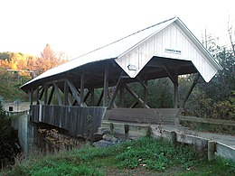 Wooden covered bridge with open sides and X-shaped beams