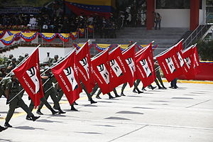 "History of Venezuela (1999–present) - Venezuelan soldiers carrying red flags with Chavéz's eyes imprinted. The text reads ""Chavez vive. La lucha sigue"" (Chavéz lives. The struggle continues)."