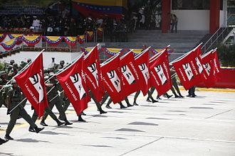 "History of Venezuela (1999–present) - Venezuelan soldiers carrying red flags with Chavéz's eyes imprinted as the text reads Chavez vive. La lucha sigue (""Chavéz lives. The struggle continues"")"