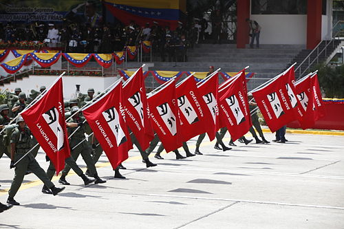 "Members of the Venezuelan armed forces carrying Chavez eyes flags saying, ""Chavez lives, the fight continues"". Chavez Vive Militar.jpg"