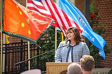 Teehee standing at a lectern with flags in the background