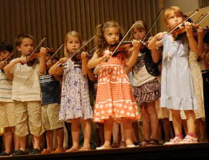 Childhood - Children playing the violin in a group recital