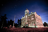 An old, two-story brick courthouse with third-story bell tower under a starry night sky.