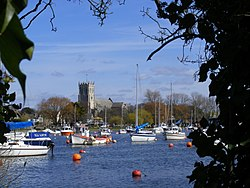 Looking across river with boats on we can see the priory against a bright blue sky