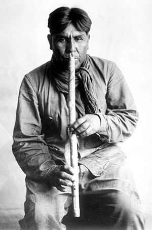 Native American flute - Cipriano Garcia playing a flute of the Tohono O'odham culture, 1919. Photograph by Frances Densmore.