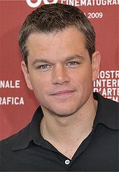 A head shot of Matt Damon, a caucasian male in his late-30s with dark hair, looking into the camera smiling slightly. He wears a black polo shirt, and stands in front of a red background with white font.