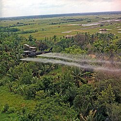 Vietnam. Defoliation Mission. A UH-1D helicopter from the  336th Aviation Company sprays a defoliation agent on a dense jungle area in the Mekong delta., July 26, 1969