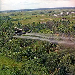 Defoliant - A helicopter sprays defoliant on a dense jungle area in the Mekong Delta (July 26, 1969).