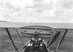 Long front-on view of military biplane on the ground, framed by upper wing, struts, cockpit and twin machine guns of similar machine facing away from camera