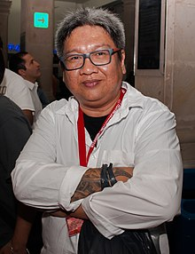A photograph of a smiling, heavyset gray-haired man wearing glasses with his tattooed arms crossed. Some bystanders are seen in the background.