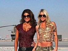 Two women posing together. The woman on the left has dark hair, and is wearing suglasses, a short-sleeved purple top, dark trousers, and a belt with a large silver buckle. The woman on the right is blonde, also wearing sunglasses, with khaki-colored trousers, and a sparkly, sequined top.