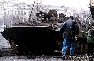 Battle of Grozny (1994–95) - A Chechen militia fighter takes cover behind a burned-out Russian BMP-2 armoured vehicle. Photo by Mikhail Evstafiev