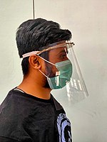 Person wearing a face shield over a green surgical mask. A simple 3D-printed face shield: curved visor, drawstring lanyard, sheet of transparent plastic curved from side to side.