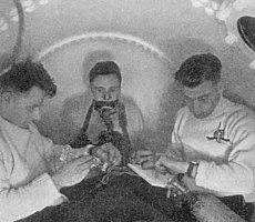 Three men inside a pressure chamber. One is breathing from a mask and the other two are timing and taking notes.
