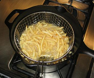 Chip pan - A cast iron chip pan with an aluminium basket being used to fry french fries.