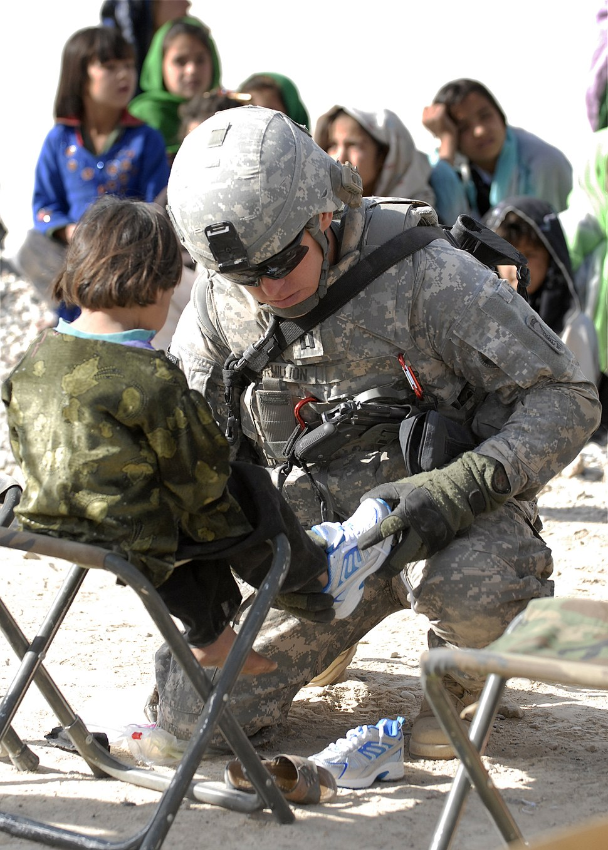 GI fits American shoes to a little Afghan boy in Zabul