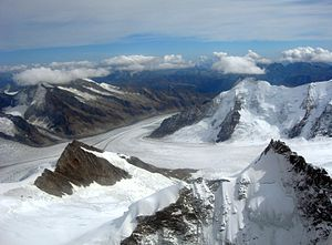 Konkordiaplatz - Aerial view of the Aletsch Glacier with the converging Jungfraufirn and Grosser Aletschfirn. Peaks of the Valais Alps on the horizon.