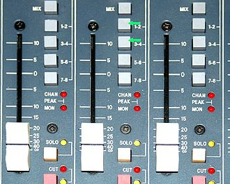 Stem mixing and mastering - Image of group assign features on individual mix channels of a mixing console. Green arrows indicate group assign buttons.